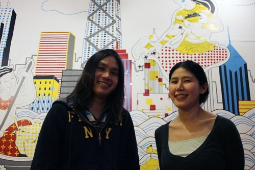 Dew Suriyawan and Noon Tosakulwong, in front of a wall depicting Thai food coming to Chicago