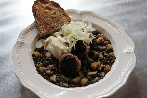 Sausage and lentils, topped with aioli and sautéed leeks.
