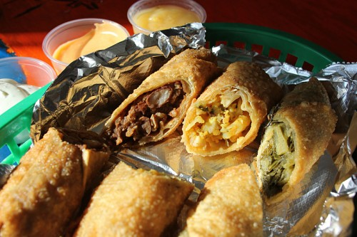 Jerk chicken, mac and cheese and greens egg rolls with dipping sauces