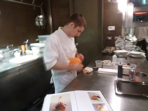 Jenner Tomaska on opening night of El Bulli, February 2012, a copy of an El Bulli cookbook open for reference