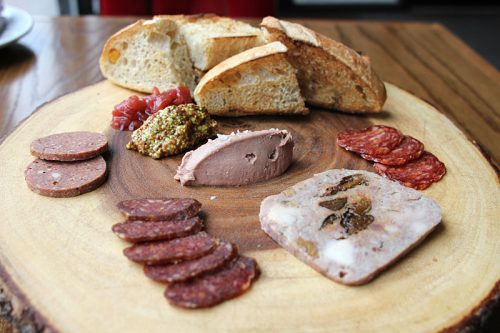 Housemade bread and charcuterie: clockwise from top, chicken liver pâté; Andalusian dry-cured chorizo; rabbit terrine with toasted walnuts, prunes and tarragon; harissa-spiced lamb salami; summer sausage, with guajillo chile and cherry lambic