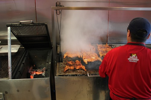 Typical setup—box for burning down charcoal to embers at left, grill with grates on pulleys (so you can raise the chicken and dump more coals in) at right. Pollo Express.