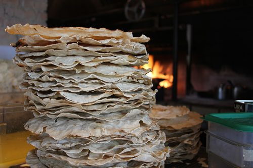Tlayudas, which are made in Oaxaca, shipped in cardboard tubes, and reheated over fire to order.